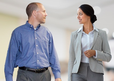 David Teknion talking to trainee with coffee mug in hand walking along side woman in business attire