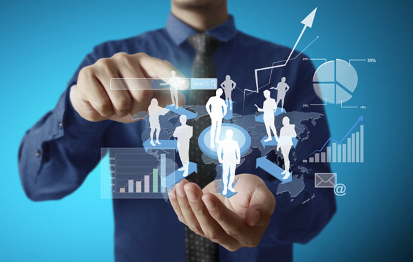 Businessman wearing a blue shirt on a blue background extends out hands to show a virtual image of white silhouettes of people and analytics data graphics floating